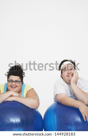 Cheerful overweight man and woman resting on exercise ball against white background - stock photo