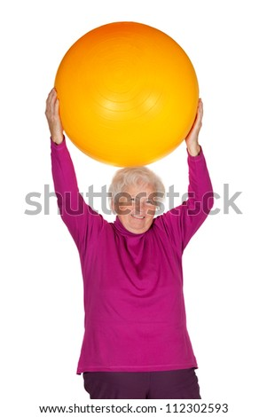 Cheerful overweight senior woman exercising with a gym ball doing pilates exercises lifting the ball above her head to improve muscle control - stock photo