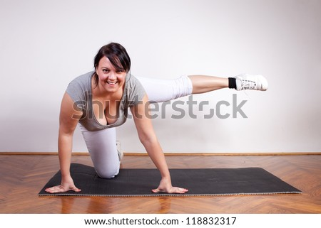 Cheerful overweight woman exercising - stock photo