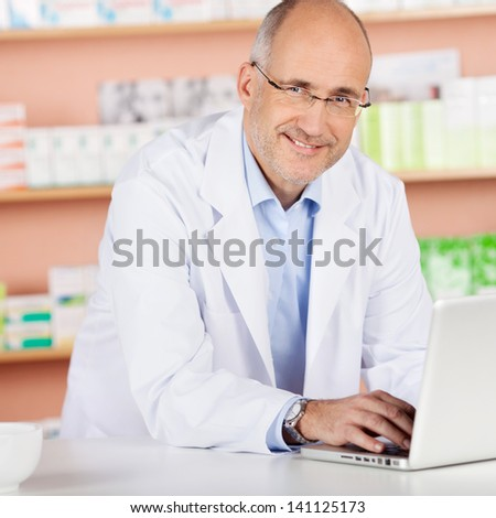 Cheerful pharmacist browsing the internet using laptop in drugstore - stock photo