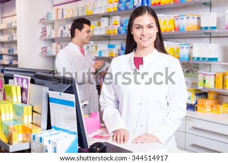 Cheerful pharmacist standing at pay desk and pharmacy technician helping  - stock photo