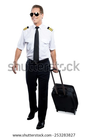 Cheerful pilot. Confident male pilot in uniform walking and carrying suitcase while being isolated on white background - stock photo