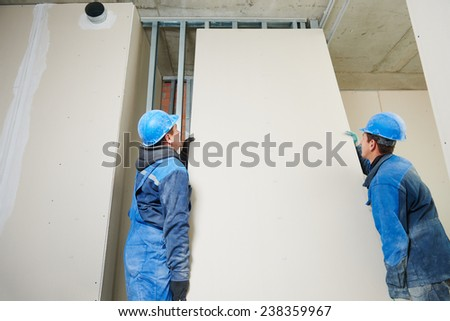 cheerful plasterboard workers team at a indoors wall insulation works - stock photo