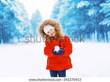Cheerful positive child with snowball having fun outdoors in winter snowy day - stock photo