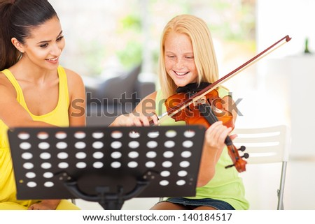 cheerful pre teen girl enjoying her violin lesson with music teacher at home - stock photo