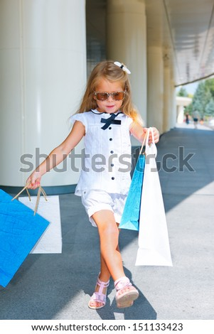 Cheerful preschool girl walking with shopping bags - stock photo