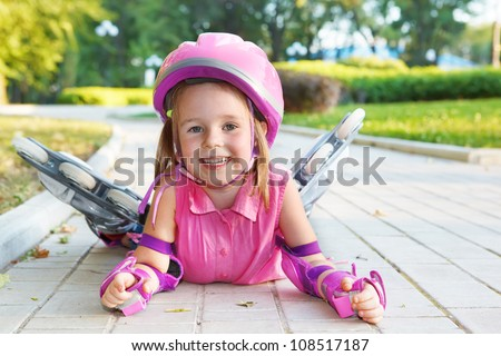 Cheerful preschool girl wearing inline roller skates and protective equipment - stock photo