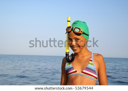 Cheerful preteen girl in diving outfit enjoying sun-bath on sea beach - stock photo