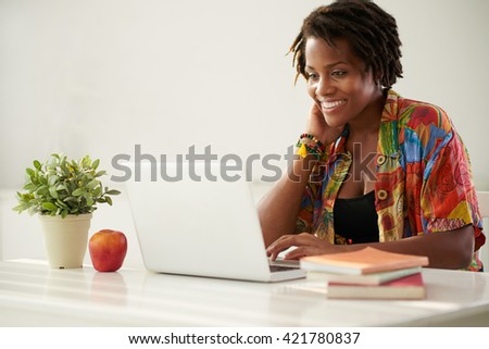 Cheerful pretty African-American woman working on computer - stock photo