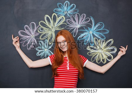 Cheerful pretty redhead young woman standing over blackboard with drawn colorful flowers behind her - stock photo