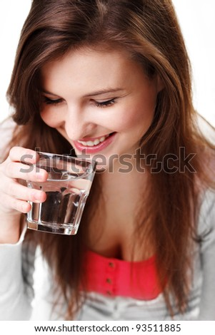 Cheerful pretty young girl holding a glass of water against white background - stock photo