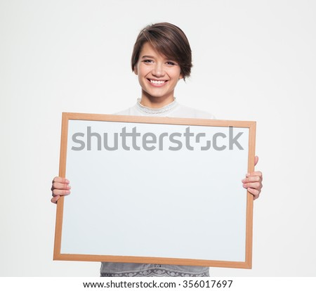 Cheerful pretty young woman holding blank board in front of herself over white background - stock photo