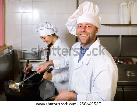 Cheerful professional chef and cook  working at take-away restaurant kitchen - stock photo