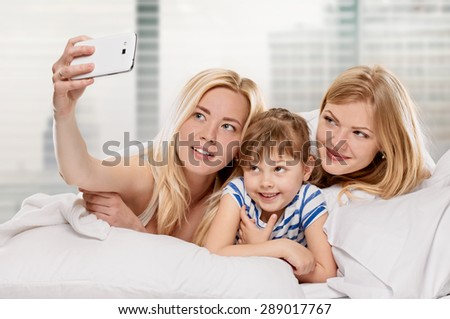 Cheerful relations girlfriends taking picture of themselves on light window background - stock photo