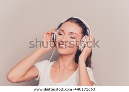 Cheerful relaxed music lover listening music in headphones - stock photo