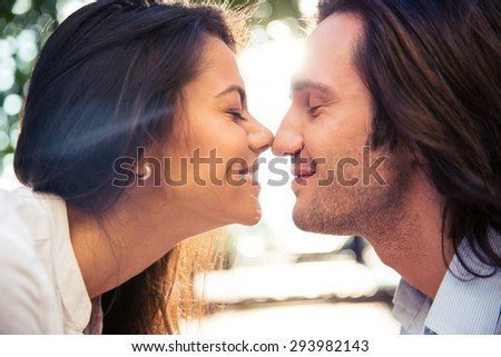 Cheerful romantic couple kissing outdoors - stock photo
