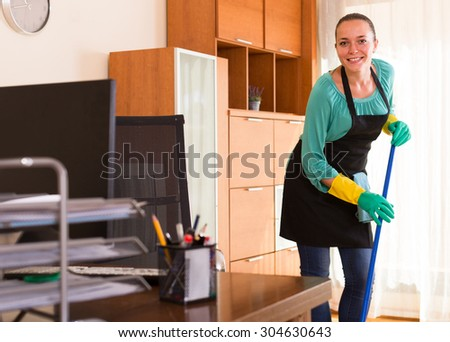 Cheerful russian cleaner  cleaning in the office-room   - stock photo
