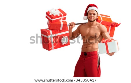 Cheerful Santa. Attractive young muscle man wearing Christmas hat presenting a gift box while holding a barbell with presents on his shoulder - stock photo