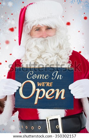 Cheerful santa claus holding page against vintage open sign - stock photo