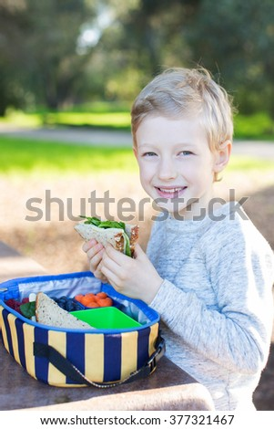 cheerful schoolboy eating healthy lunch during recess at school - stock photo