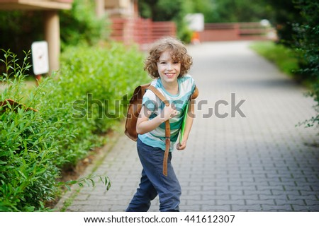 Cheerful schoolboy. The boy of 8-9 years looked back and with a cheerful smile looks in the camera. It has fair curly hair and blue eyes. In hands the bright folder, behind the back - a satchel. - stock photo