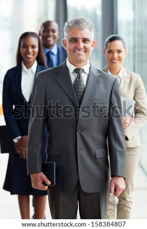 cheerful senior business leader standing in front of his team in office - stock photo