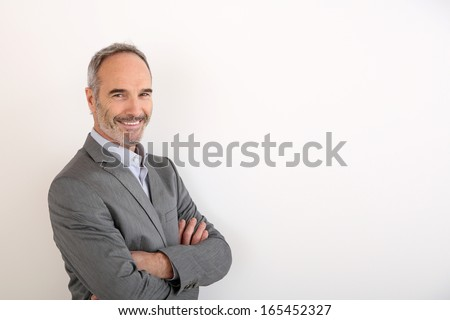 Cheerful senior businessman standing on white background - stock photo