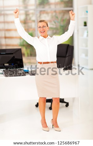 cheerful senior businesswoman waving fists in office - stock photo
