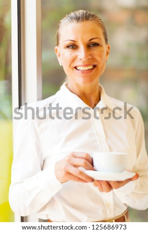 cheerful senior businesswoman with coffee in office - stock photo