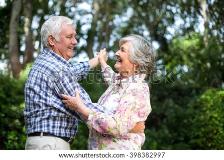 Cheerful senior couple dancing against trees in back yard - stock photo