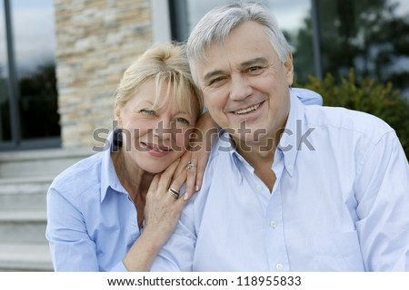 Cheerful senior couple looking at camera - stock photo