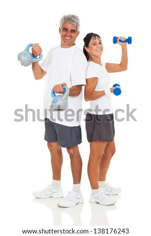 cheerful senior couple posing with various gym equipment on white background - stock photo