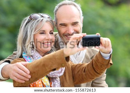 Cheerful senior couple taking picture with smartphone - stock photo