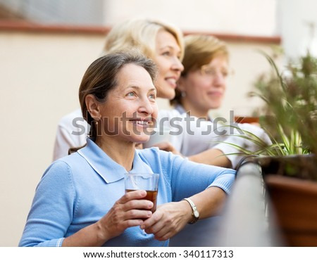 Cheerful senior female colleagues having lunch break at patio and drinking tea - stock photo