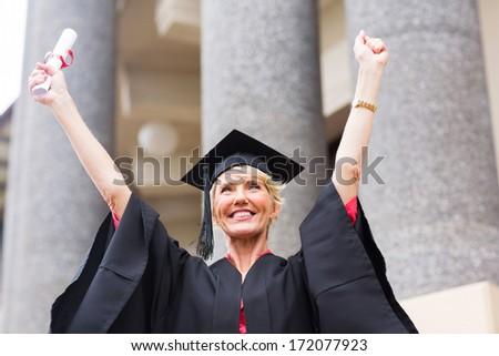 cheerful senior female university graduate arms up - stock photo