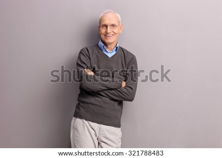 Cheerful senior gentleman leaning against a gray wall and looking at the camera  - stock photo