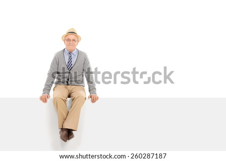 Cheerful senior gentleman sitting on a blank panel isolated on white background - stock photo