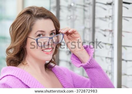 Cheerful senior lady is buying new eyewear  - stock photo