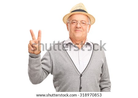 Cheerful senior man gesturing peace sign with his hand and looking at the camera isolated on white background - stock photo