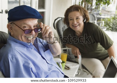 Cheerful senior man holding sunglasses with woman in background - stock photo