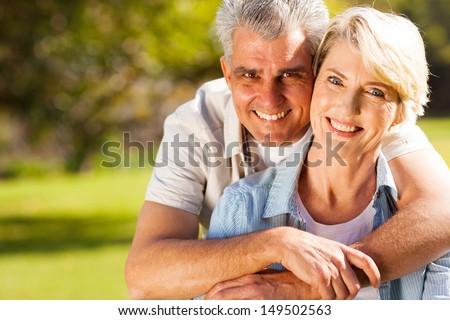 cheerful senior man hugging wife outdoors - stock photo