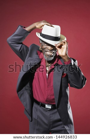 Cheerful senior man in suit adjusting fedora against red background - stock photo