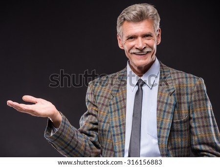 Cheerful senior man is showing something, isolated on dark background. - stock photo