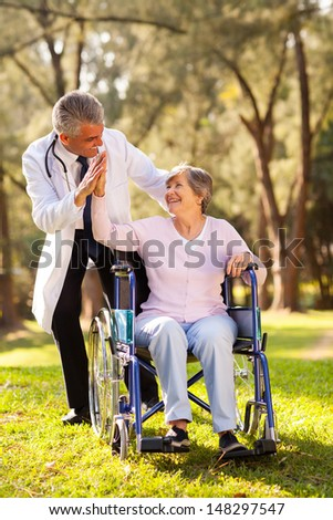 cheerful senior patient doing high-five with friendly caregiver outdoors - stock photo