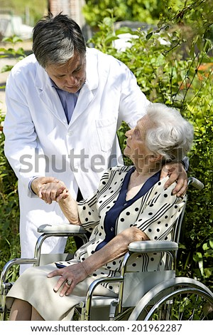 cheerful senior patient in wheelchair with  friendly caregiver outdoors  - stock photo