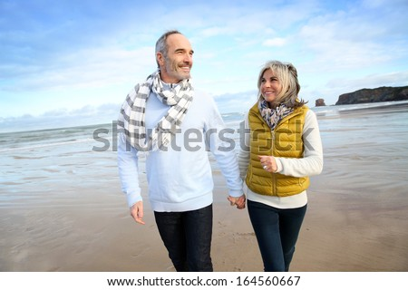 Cheerful senior people walking on the beach - stock photo