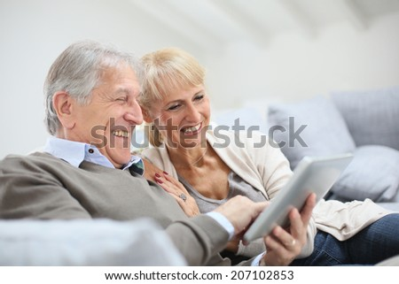 Cheerful senior people websurfing on internet with tablet - stock photo