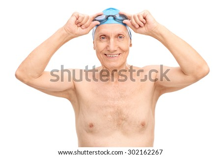 Cheerful senior with a blue swim cap putting on his swimming goggles and looking at the camera isolated on white background - stock photo