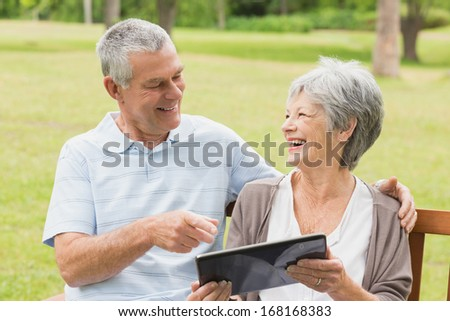 Cheerful senior woman and man using digital tablet on bench at the park - stock photo