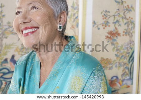 Cheerful senior woman in bathrobe looking up against white background - stock photo